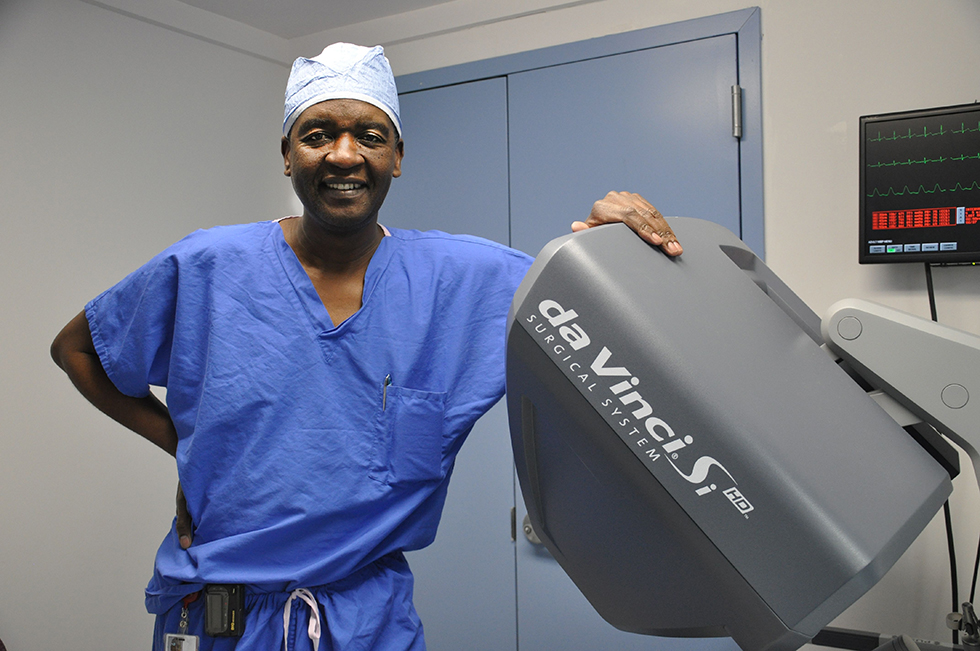 Dr Mushayandebvu standing next to da Vinci surgical machine