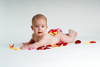 Photo of a baby sprawled on colorful petals