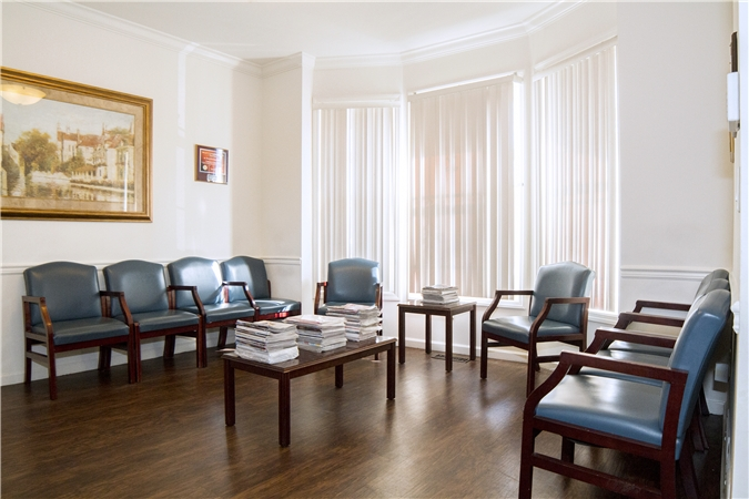 Photo of our waiting room: chairs by bay windows and dark hardwood flooring